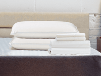 Pillows and sheets laying on a cocoon memory foam mattress