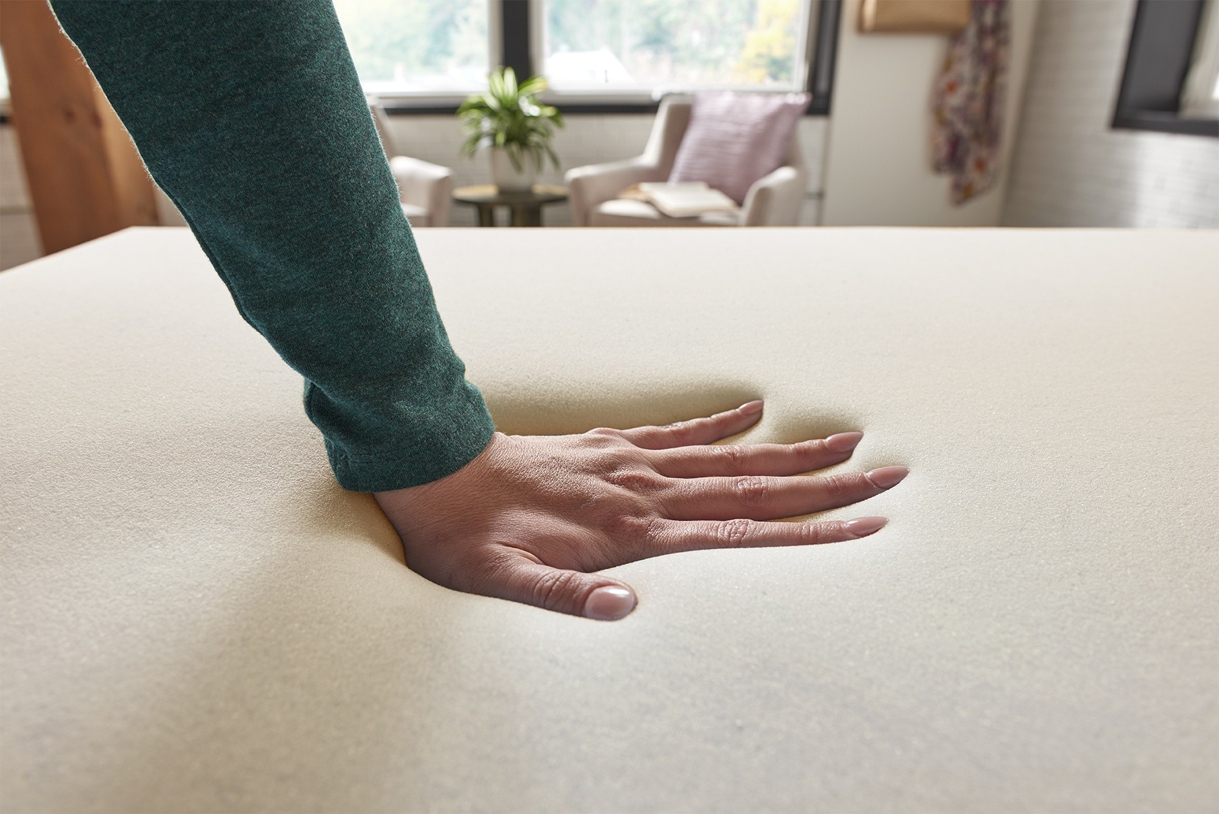 Woman pressing down on the 2 inch memory foam topper