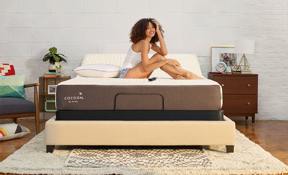 A girl sitting on a chill mattress, elevated by an Ease base